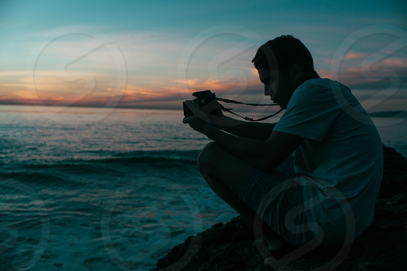 man sitting on cliff photography photo