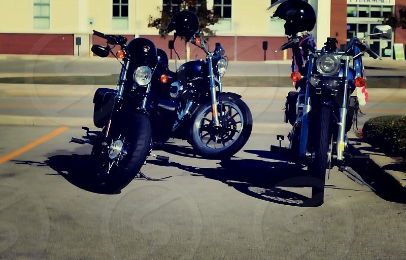 Three parked motorcycles with helmets photo