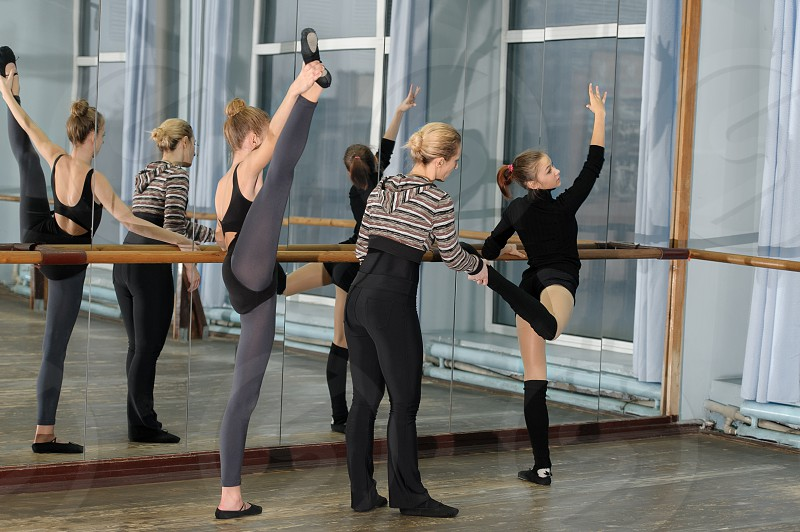 Choreographer helping young ballet dancer to have right position. Exercising at the barre by the mirror photo