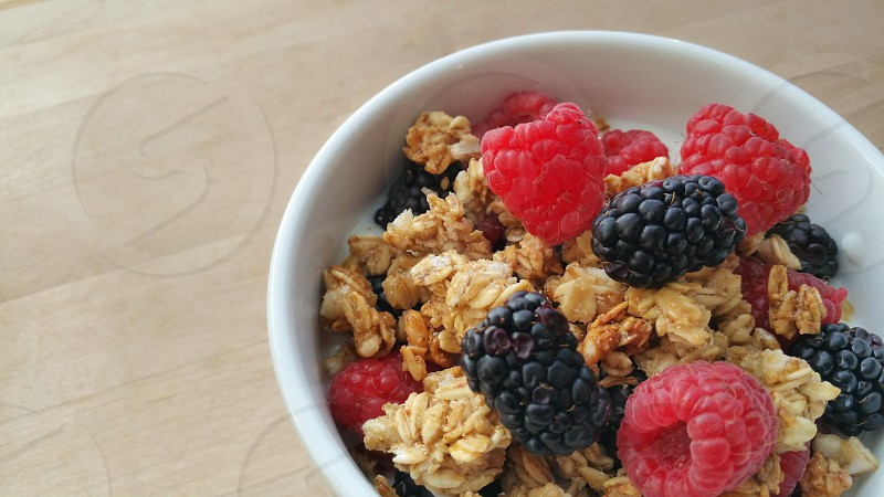 A bowl filled with raspberries blackberries granola and yogurt. photo