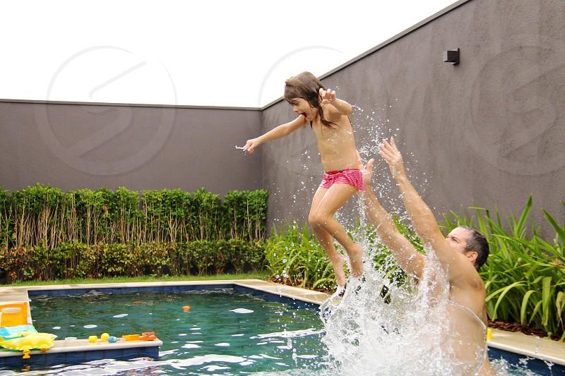 man throwing girl in swimming pool photo