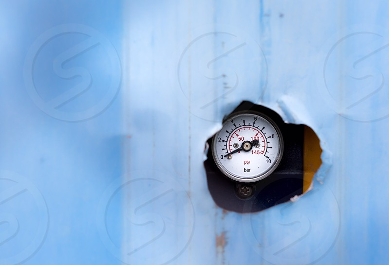 A meter through a hole of a construction wall in Shanghai photo