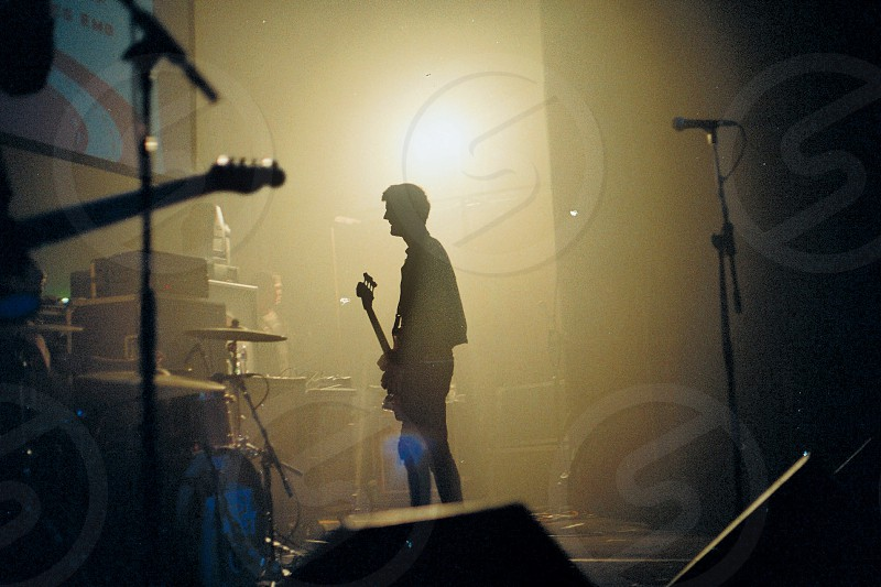 man with bass guitar standing photo