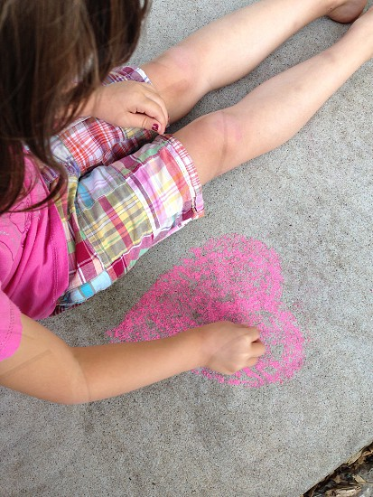 Girl drawing chalk heart on sidewalk photo