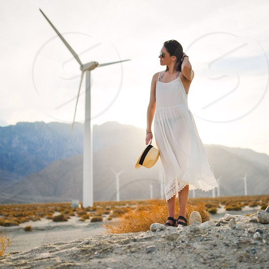 woman in white cami dress in front on electric windmill photo