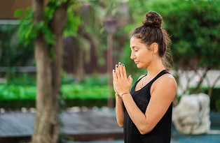 Unrecognizable young woman working outdoors, doing yoga