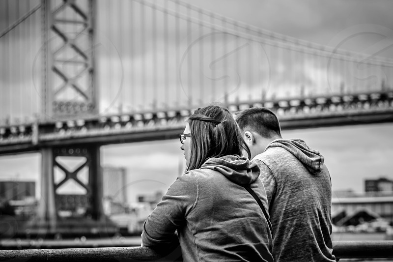 couple standing on bridge photo