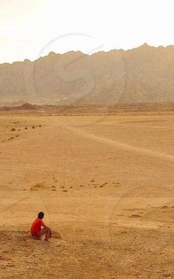 man in orange t shirt on sand dune photo