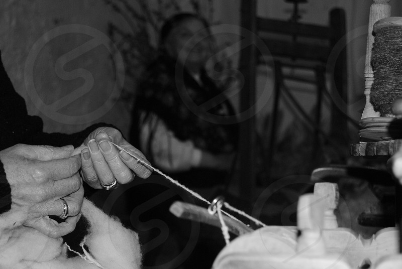 person holding string weaving in grayscale photo