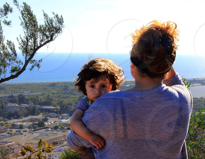 Kid parent child boy mom view sad serious face landscape portrait Ventura California Cali coast pacific ocean sky water hug hold holding held love cute beautiful hill mountain  photo