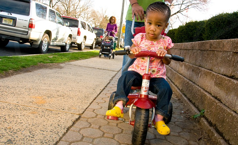 girl in blue denim jeans riding a trike toy photo