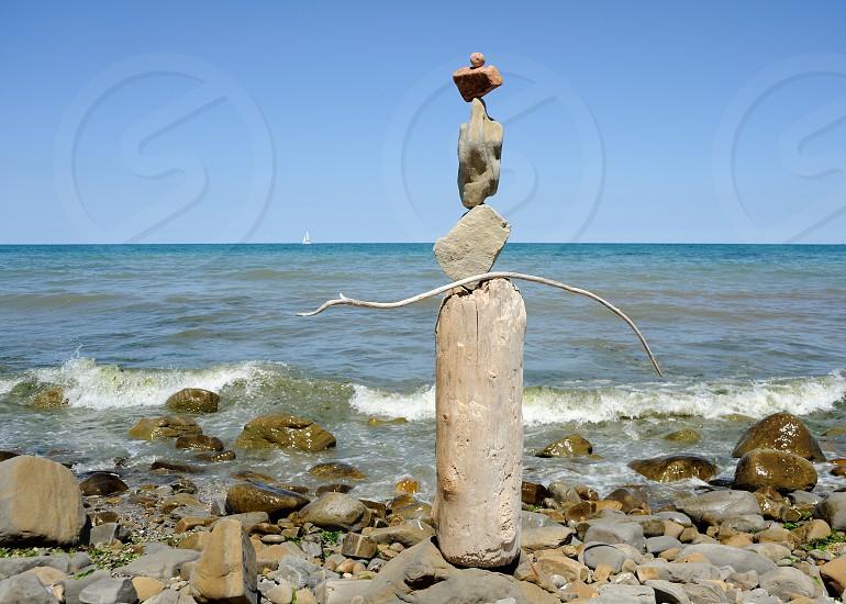 gray rock balancing on shore photo