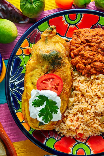 Chili relleno chili peppers filled with cheese in dish with with rice and frijoles beans photo