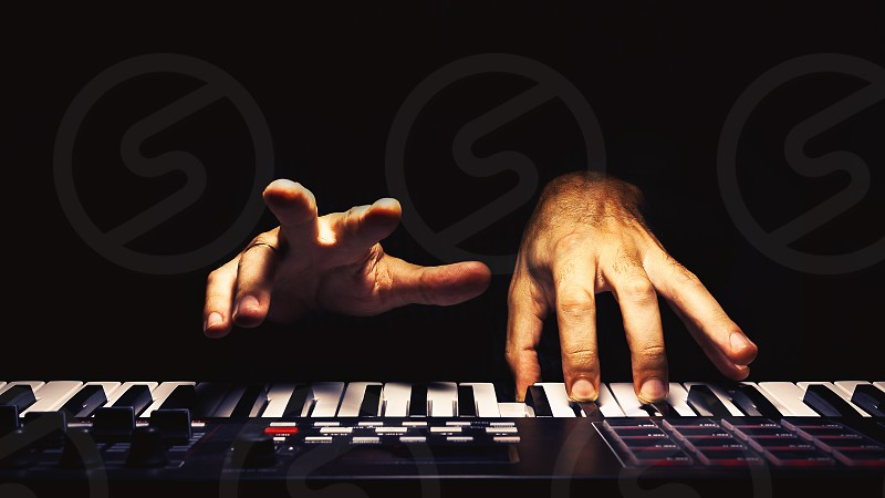 Playing a keyboard illuminated and accentuated view on hands. photo