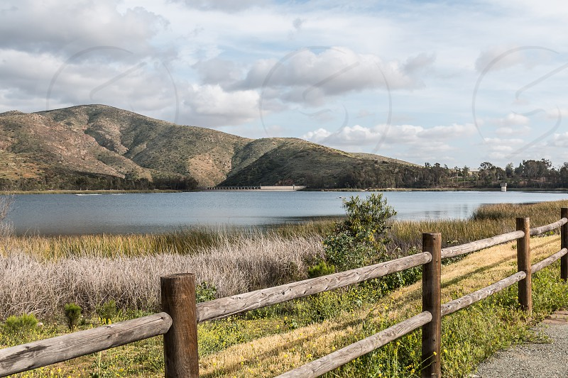 A mountain range with a lake and fence line on a cloudy day. photo