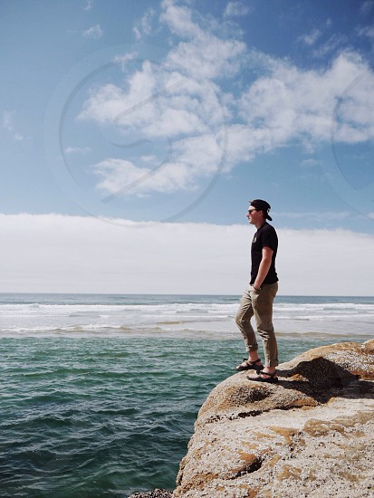 man standing on rock over water photo