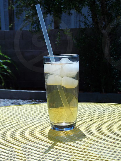clear beverage glass with ice cubes and drinking straw photo