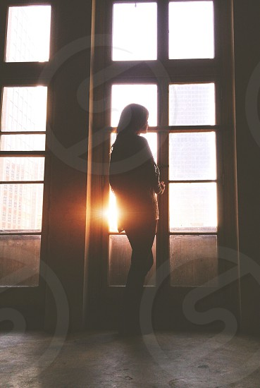 silhouette of person looking at window photo