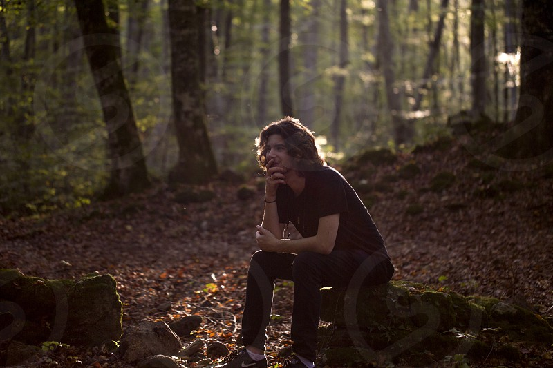 A young man is sitting on a moss-covered stone in a beech forest. photo