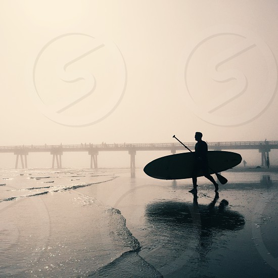 man holding surfing board and walking towards to water photo