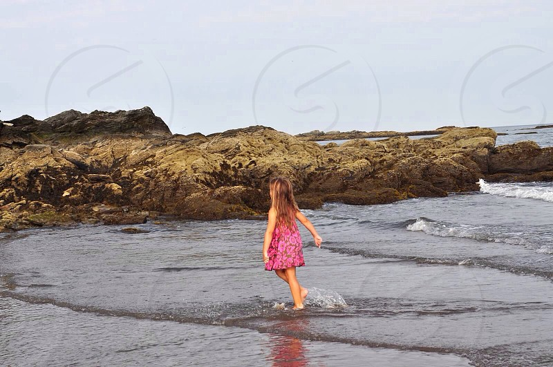 girl wearing pink dress walking in water during daytime photo