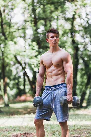 Young muscular man posing with weights outdoors photo