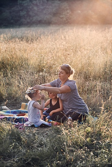 Family spending time together on a meadow close to nature parents and children playing together making coronet of wild flowers. Candid people real moments authentic situations photo
