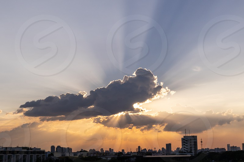 Sunbeam through the dramatic cloud during sunset time with silhouette building below photo