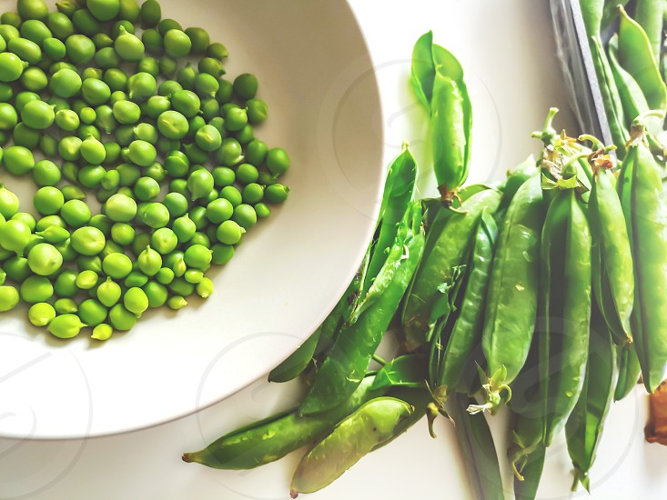 green peas freshly removed from the pod on a white plate. Agriculture and vegetables. Healthy food and lifestyle. photo