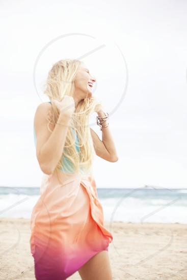 blonde smiling woman wearing a peach dress on a beach photo