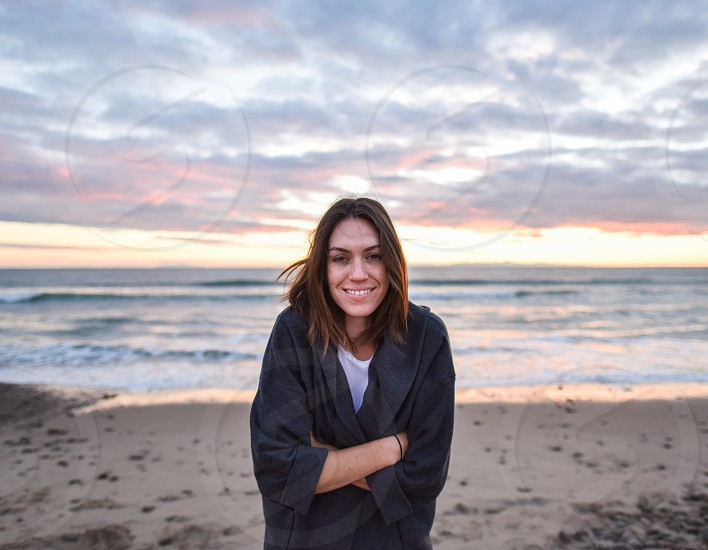 woman smiling wearing black jacket standing on beach near body of water photo