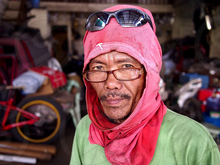 ANTIPOLO CITY PHILIPPINES - FEBRUARY 21 2019: A carpenter wearing a shirt on his head as protective gear poses for the camera. photo