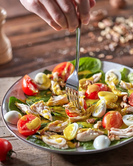 Female hands hold a fork above the plate with healthy fresh cooked salad and on a wooden background. Concept of healthy diet food. photo