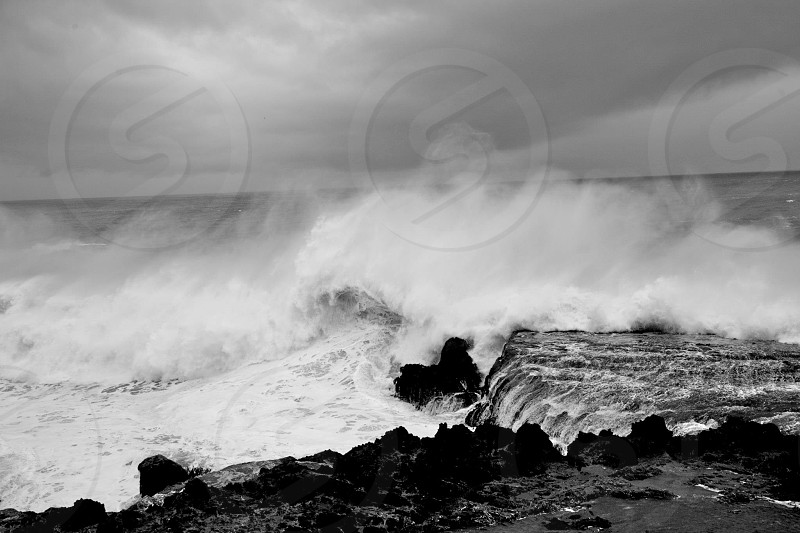 sea waves crashing on rocky beach shore in black and white photograph photo
