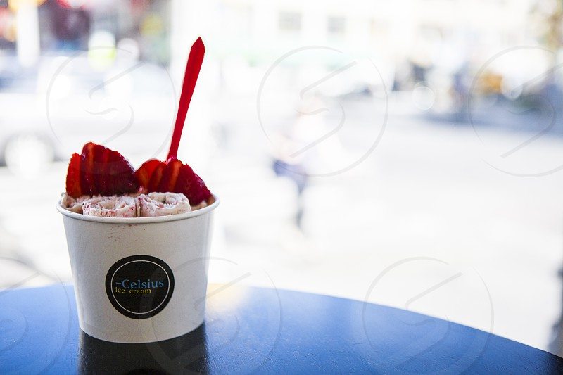 focus photo of a celsius ice cream with sliced strawberry toppings during daytime photo