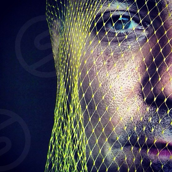 man's face with yellow net photo