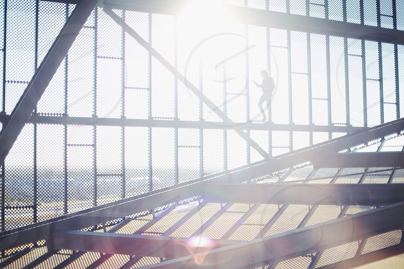 person's silhouette on metal bars photo