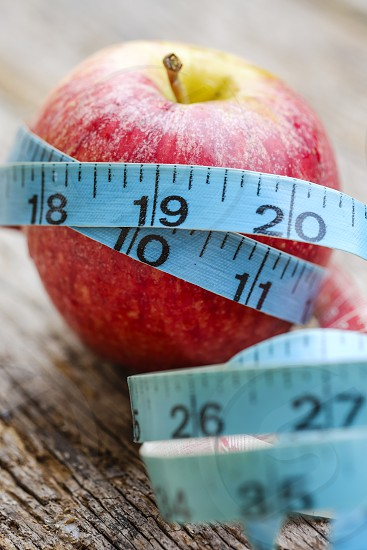Close-up of red apple wrapped with measurement tape on old wooden tabletop photo