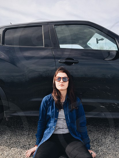 woman leaning on to a black passenger vehicle photo