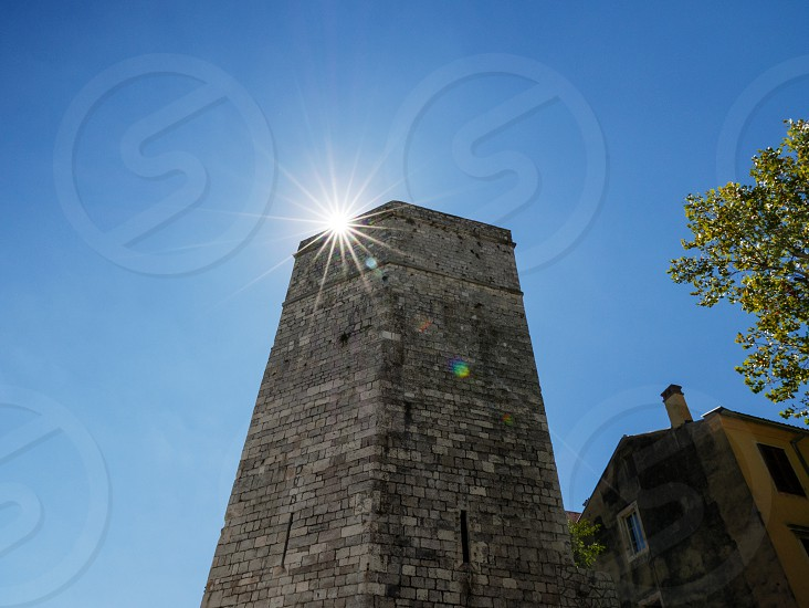 Sunburst behind a stone tower. Natural light. Clear skies. photo
