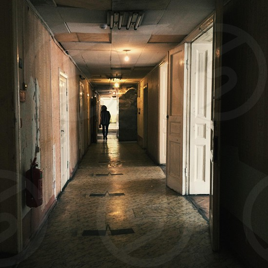 Corridor or hallway in old brim down building with silhouette of person in distance photo