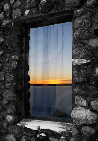 Sunset on frozen lake horizon reflected in cottage window in winter photo