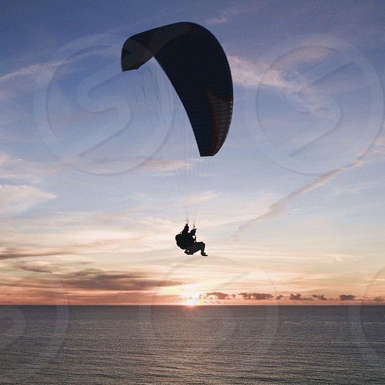person on parachute near sea water photo