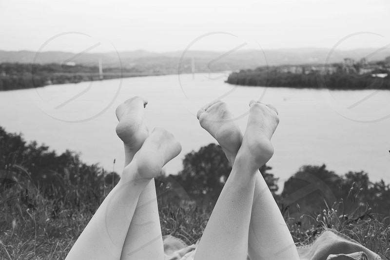 Two friends laying on top of the hill above river and holding legs crossed up in the air monochrome effect. photo