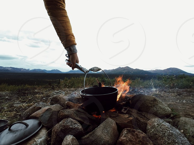 Cooking in Wild outside cooking cast iron fire open fire camping adventure landscape  photo