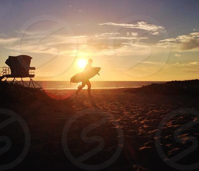 man carrying surfboard on beach photo