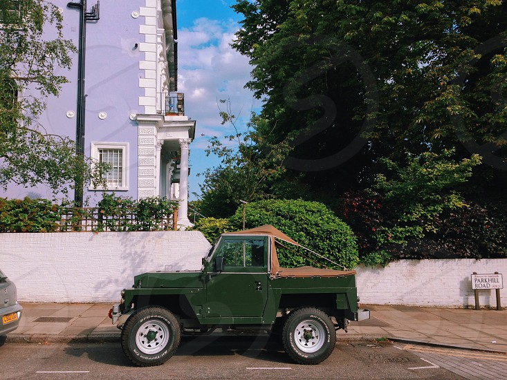 green jeep parked against green hedge and white concrete wall under purple and white concrete building and green tall trees at daytime photo