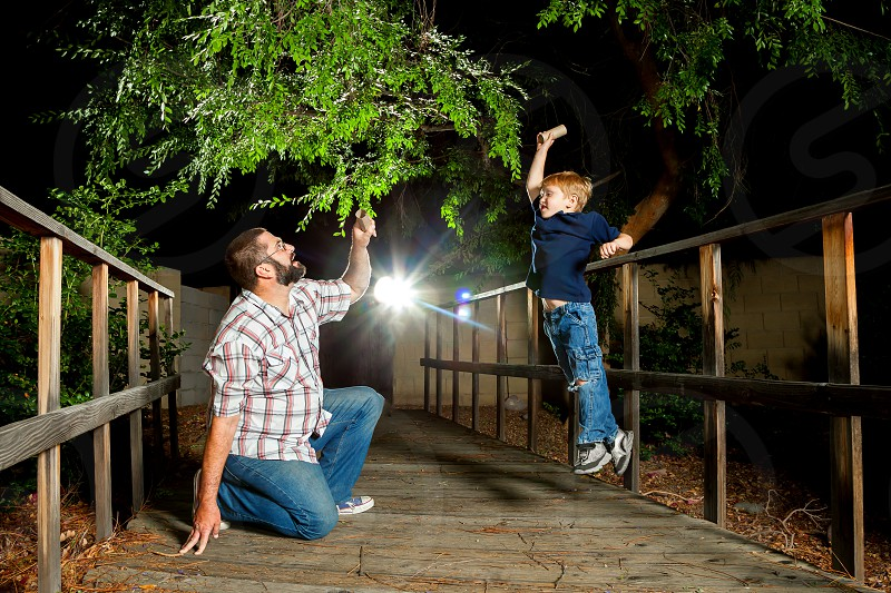 """A father and his son play with pretend """"swords"""" that are really toilet paper rolls.  It is nighttime on a bridge with a light burst behind them. photo"""