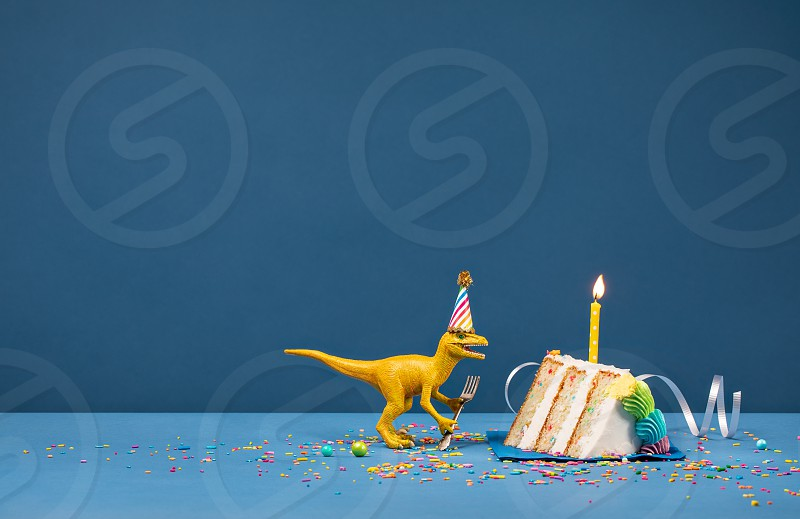 Toy Dinosaur holding a fork and blowing out a Birthday candle on a blue background photo