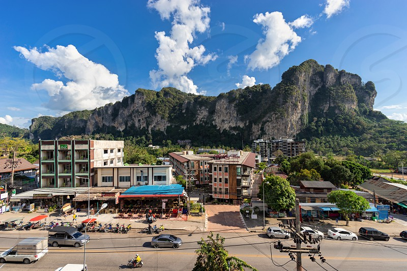 Ao Nang Krabi Province Thailand - January 13 2019: View from the height on local main road and street with hotels restaurants big cliff and clouds on blue sky in sunny day photo